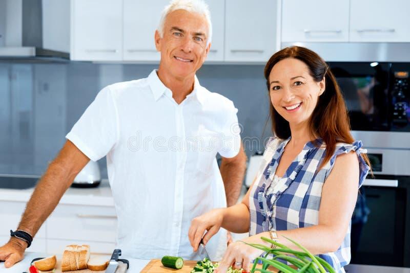 Rijp paar die thuis koken stock afbeeldingen