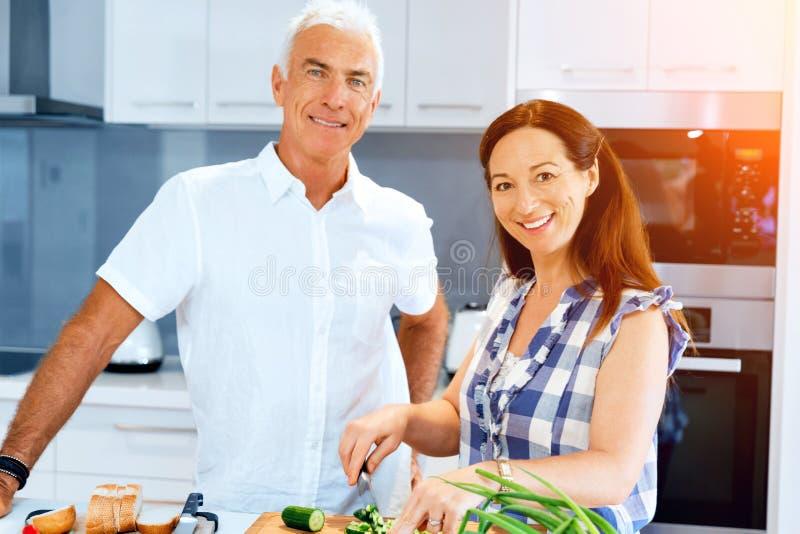 Rijp paar die thuis koken stock foto