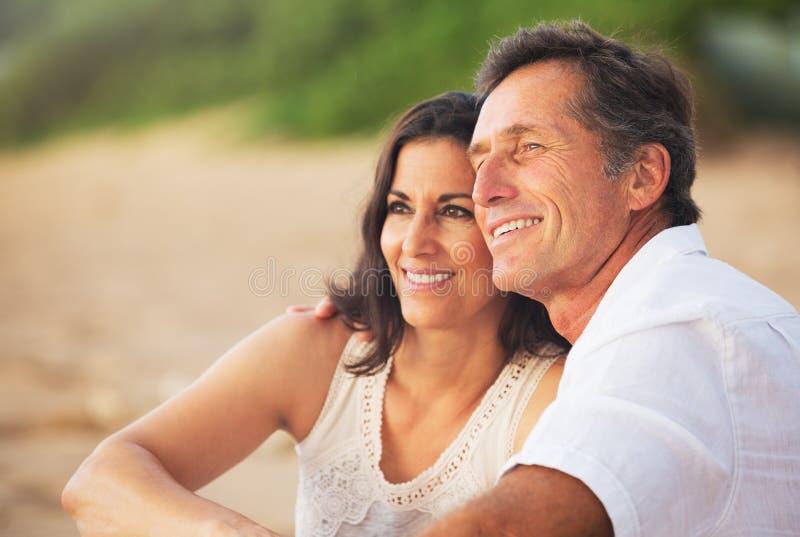Rijp Paar die van Zonsondergang op het Strand genieten royalty-vrije stock afbeeldingen