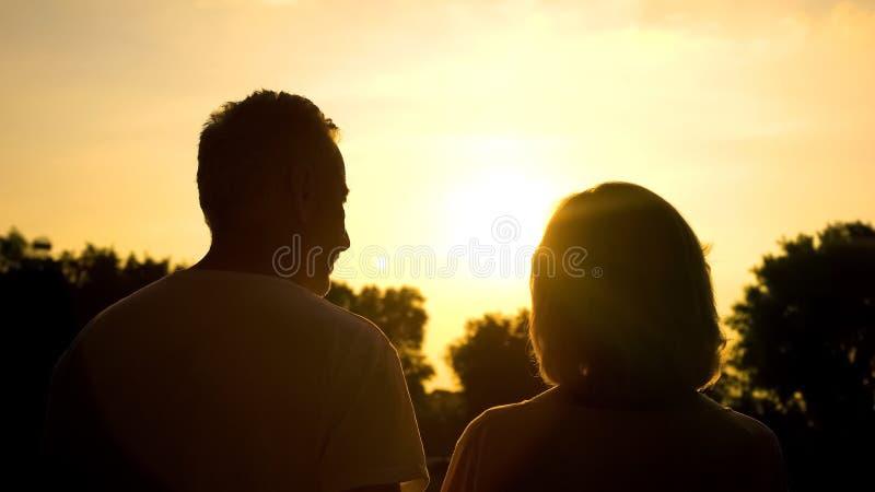 Rijp paar het letten op zonsondergangplatteland, aardkalmte, pensioenvrije tijd royalty-vrije stock foto's