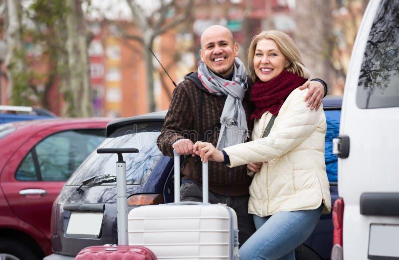 Rijp paar met bagage bij straat stock foto