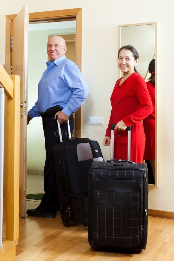 Rijp paar met bagage in huis royalty-vrije stock afbeeldingen
