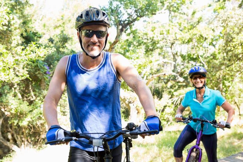 Rijp paar met zonnebril die fiets berijden stock afbeelding