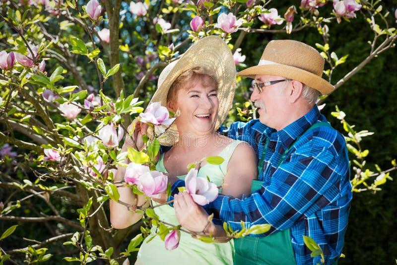 Rijp paar in sunhats die in tuin, het koesteren en het glimlachen omhelzen stock afbeeldingen