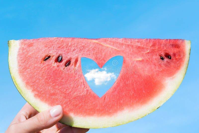 Rijp stuk van watermeloen met het gat van de hartvorm in vrouwelijke handen op de achtergrond van de blauwe hemel met weinig wolk stock afbeelding