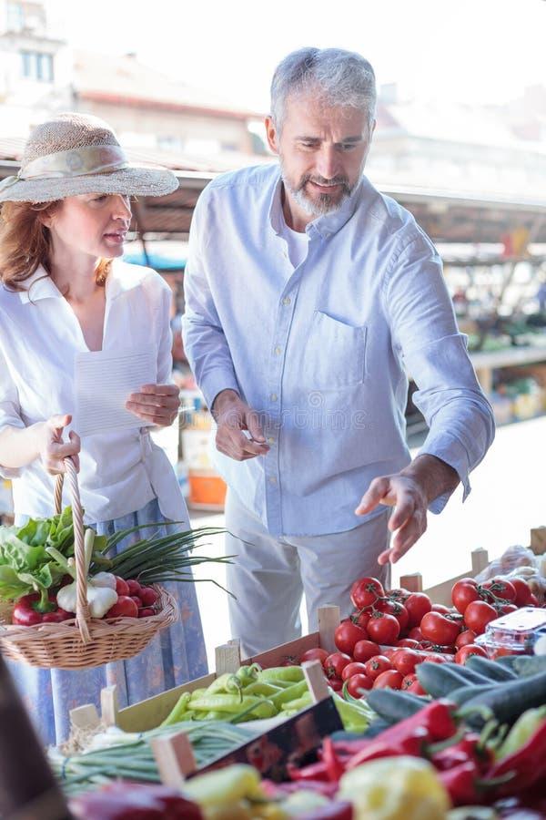 Rijp volwassen paar die verse organische groenten in een lokale markt kopen stock afbeelding