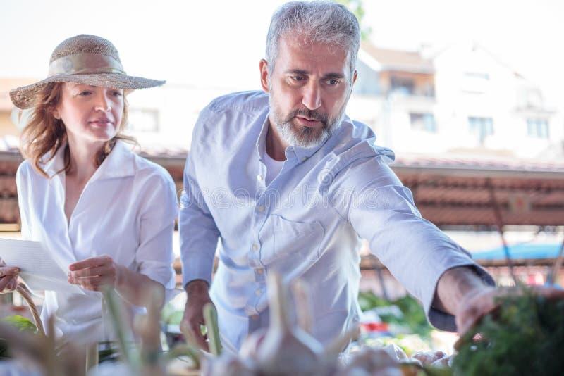 Rijp volwassen paar die verse organische groenten en kruidenierswinkels in een markt kopen stock afbeeldingen