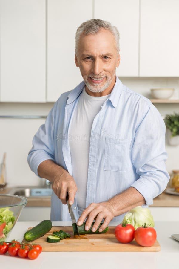 Rijpe aantrekkelijke mens die zich bij keuken het koken bevinden royalty-vrije stock fotografie