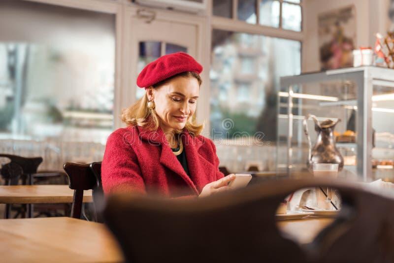 Rijpe aantrekkelijke modieus vrouwengevoel ontspannen zitting in bakkerij op weekend stock afbeelding