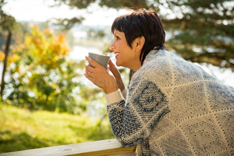 Rijpe aantrekkelijke vrouw die zich op terras met kop van hete koffie bevinden royalty-vrije stock fotografie