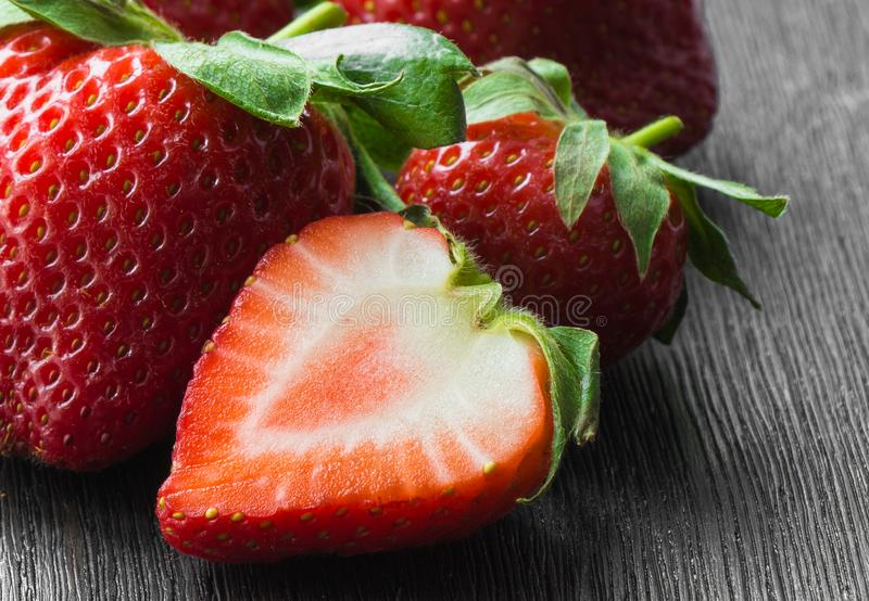 Rijpe aardbeien, rood, geheel, half, close-up op een donkere achtergrond stock afbeelding