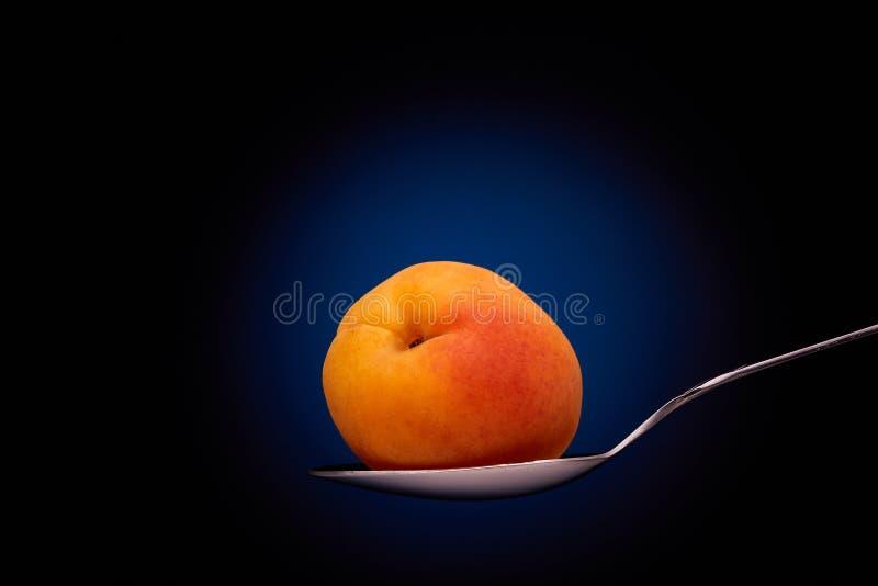 Rijpe abrikoos op een lepel stock foto