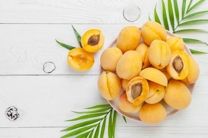 Rijpe abrikozen op een ronde plaat op een witte raadslijst Vlak-leg stock fotografie