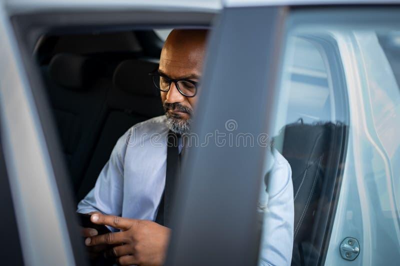 Rijpe Afrikaanse zakenman die smartphone in auto gebruiken royalty-vrije stock foto