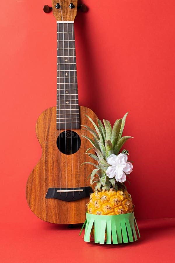 Rijpe ananas in een groene rok Gitaar op een modieuze koraalachtergrond Ontspanningsconcept en Hawaiiaanse partij royalty-vrije stock foto