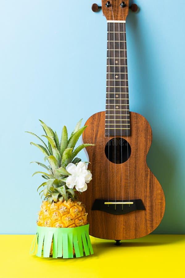 Rijpe ananas groene rok, gitaar op een heldere blauwe gele achtergrond r royalty-vrije stock afbeeldingen