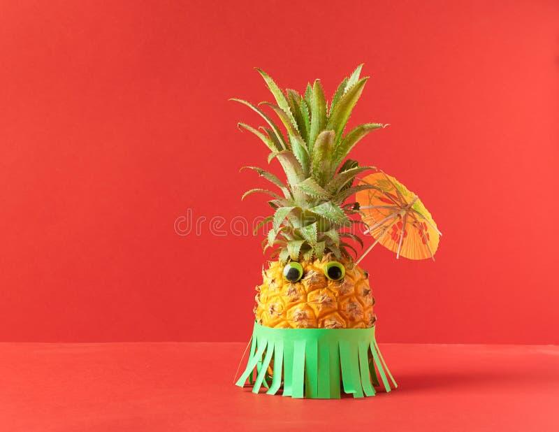 Rijpe ananas met ogen en een Hawaiiaanse groene rok en paraplu op een in koraalachtergrond De vakantieconcept van de zomer royalty-vrije stock fotografie