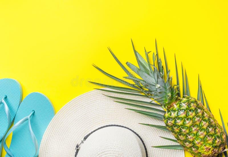 Rijpe ananas op groene de hoeden blauwe pantoffels van het palmblad witte stro op heldere gele stevige achtergrond De pret van de royalty-vrije stock fotografie
