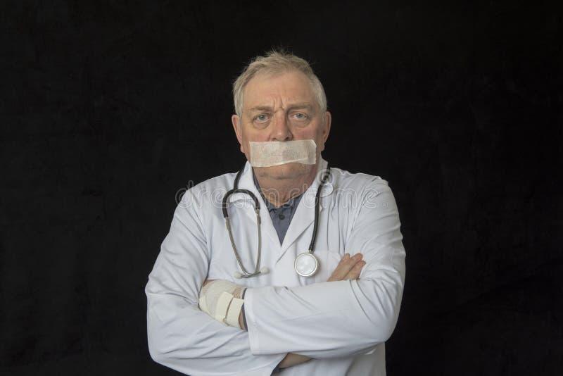 Rijpe arts met band over zijn mond royalty-vrije stock foto