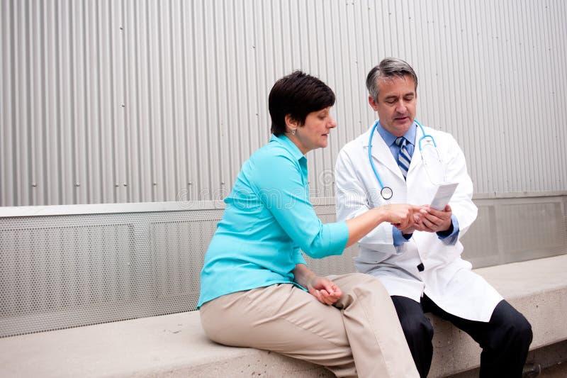 Rijpe arts met vrouwelijke patiënt stock fotografie