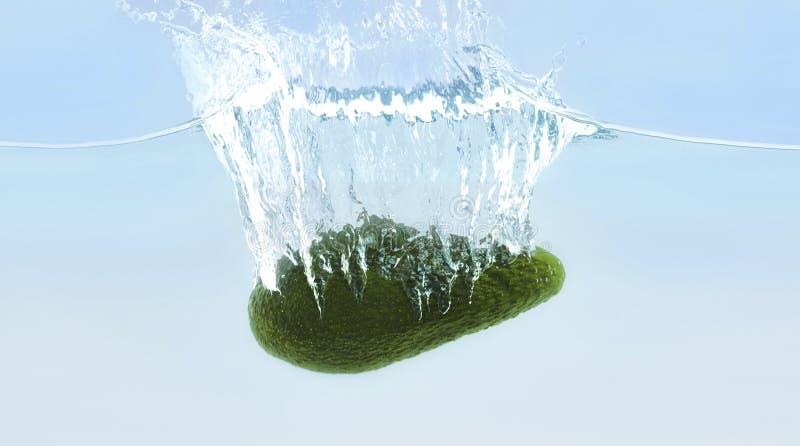 Rijpe avocado die in water met bellen dalen royalty-vrije stock fotografie