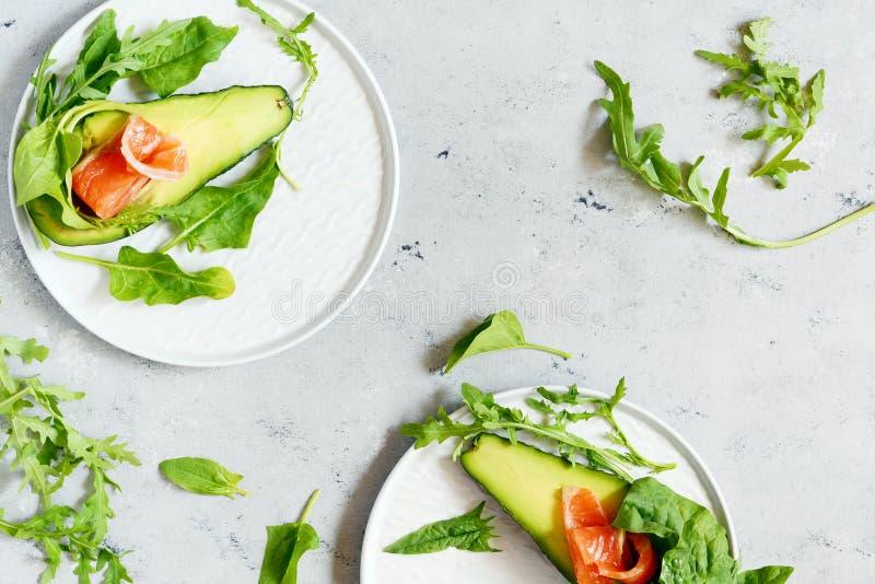 Rijpe avocadoboten met plakken van gezouten forel, zalm en verse greens op een grijze achtergrond Avocadoboten met zalm worden ge stock fotografie