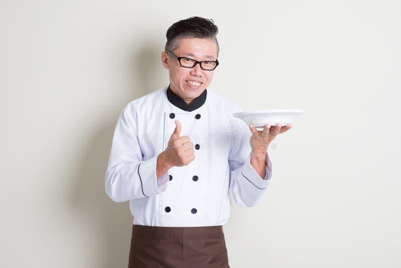 Rijpe Aziatische Chinese chef-kok die schotel en duim omhoog voorstellen stock afbeelding