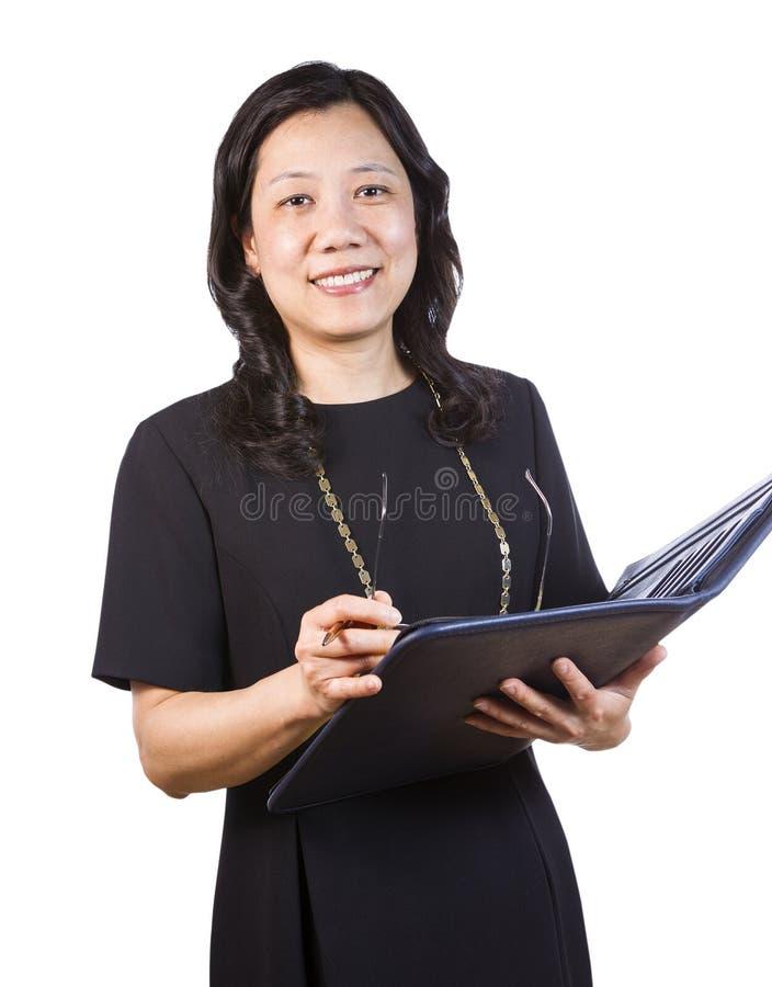 Rijpe Aziatische Vrouw in Bedrijfskledij met notastootkussen en glazen stock fotografie