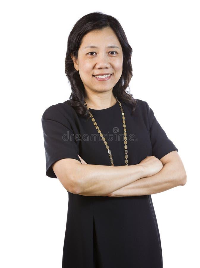 Rijpe Aziatische Vrouw in Bedrijfskledij ontspannen status stock foto