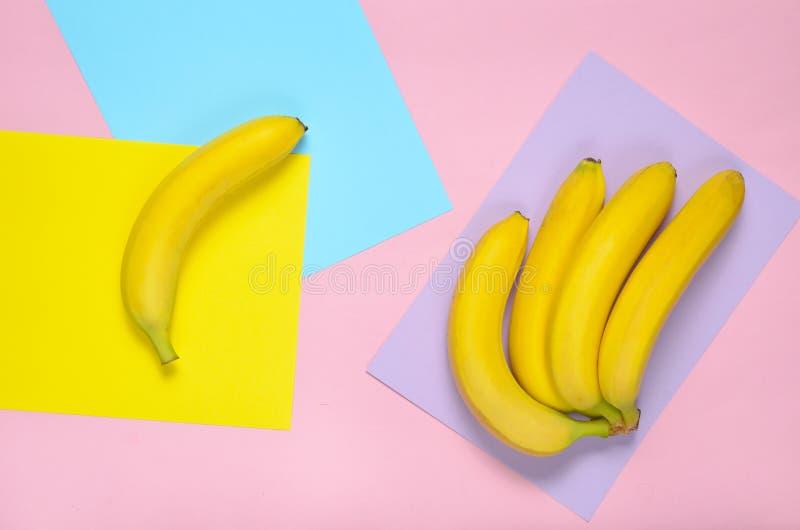 Rijpe bananen op een gekleurde document achtergrond Pastelkleurtendens Het concept uniciteit Minimalism, hoogste mening stock foto