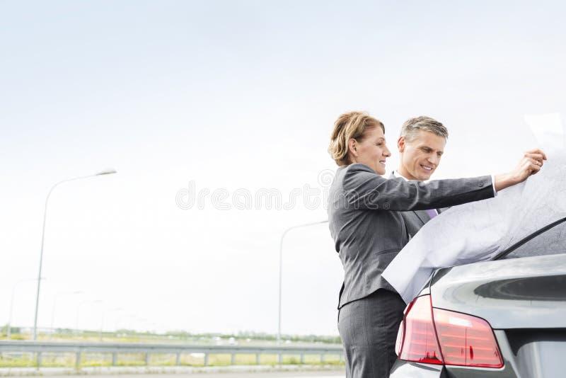 Rijpe bedrijfscollega's die kaart buiten auto analyseren tegen hemel stock fotografie