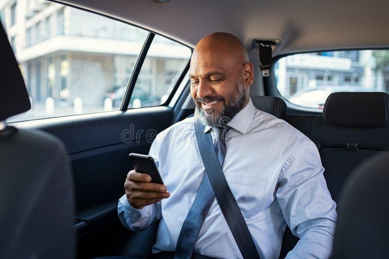 Rijpe bedrijfsmens die telefoon in auto met behulp van royalty-vrije stock afbeelding