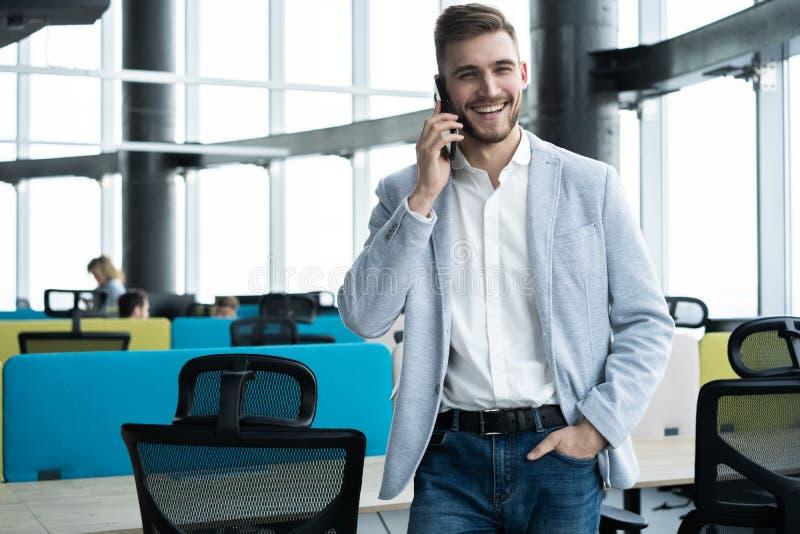 Rijpe bedrijfsmens die zich binnen de bureaubouw bevinden en celtelefoon met behulp van royalty-vrije stock afbeeldingen