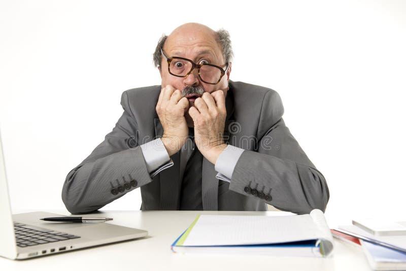 Rijpe bedrijfsmens met kaal hoofd bij zijn jaren '60 werken beklemtoond en gefrustreerd bij laptop van de bureaucomputer bureau d royalty-vrije stock fotografie