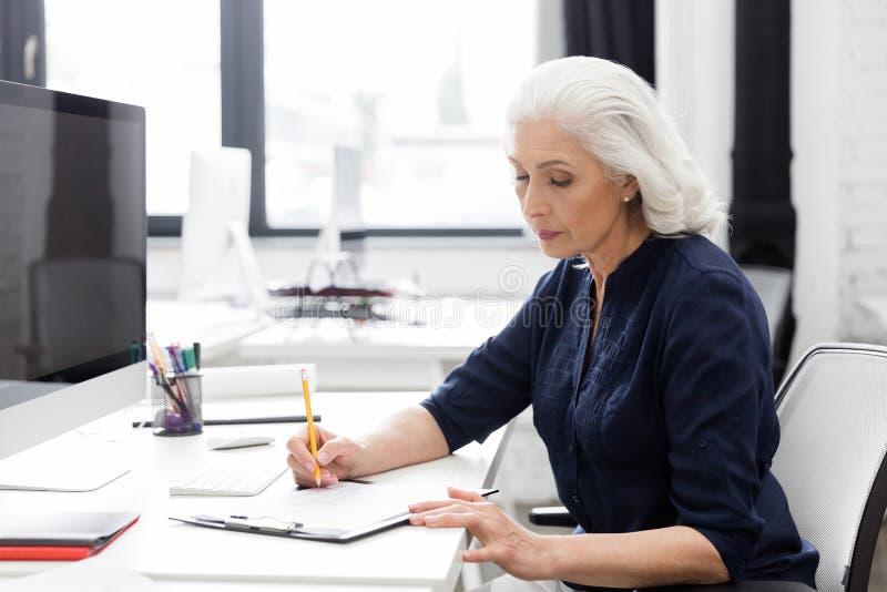 Rijpe bedrijfsvrouw die nota's over een stuk van document maken royalty-vrije stock fotografie