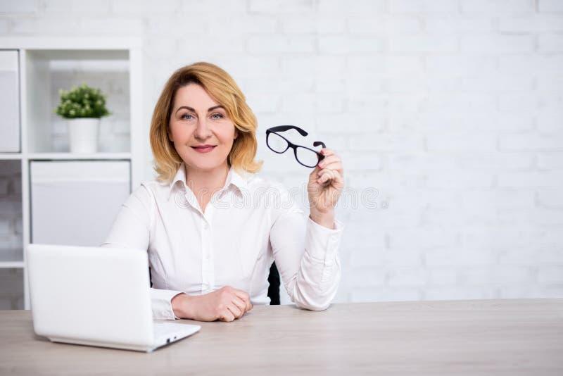 Rijpe bedrijfsvrouwenzitting met laptop in moderne bureau of woonkamer - kopieer ruimte over witte muur stock afbeelding