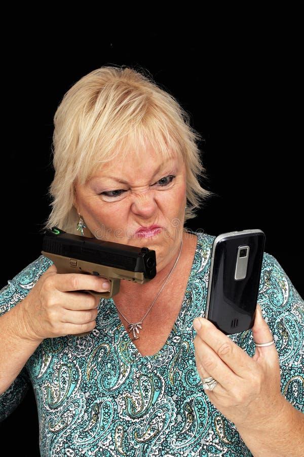 Rijpe Blonde met Telefoon van de Cel en een Pistool (1) stock foto