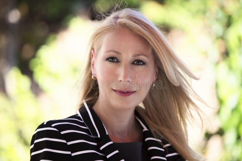 Rijpe blonde vrouw die bij de camera glimlachen royalty-vrije stock afbeelding