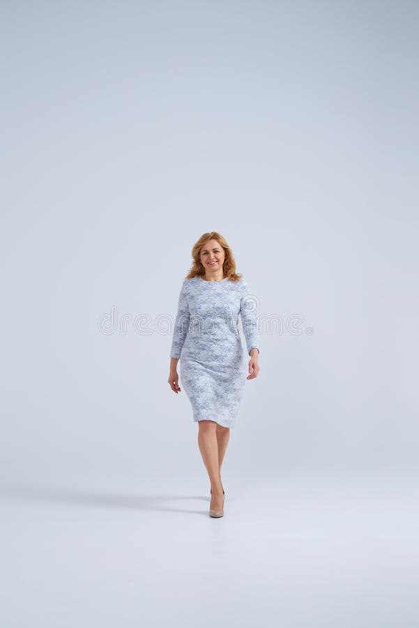 Rijpe blonde vrouw die en op camera glimlachen wolking stock afbeeldingen