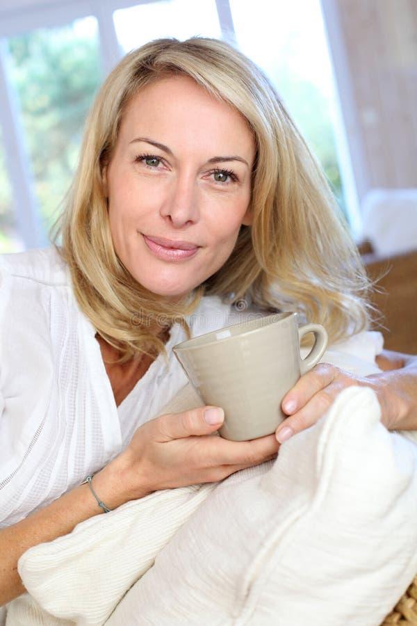 Rijpe blonde vrouw met kop thee royalty-vrije stock foto's