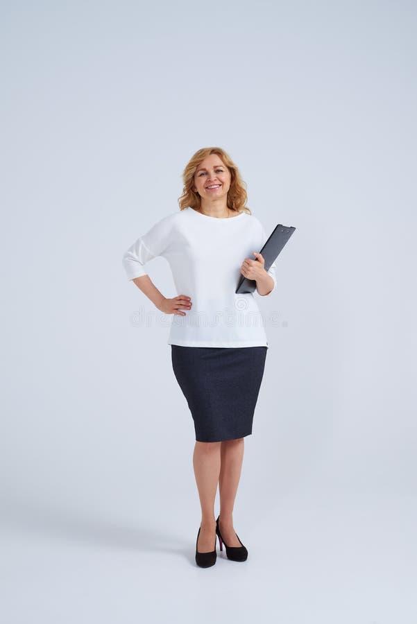 Rijpe blonde vrouw met omslag die zich in studio bevinden stock afbeelding