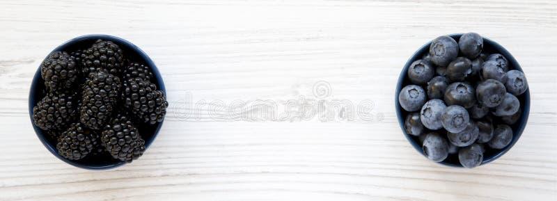 Rijpe braambessen en bosbessen in blauwe kommen op witte houten achtergrond, luchtmening De zomerbes Van hierboven, vlak, bovenka royalty-vrije stock fotografie
