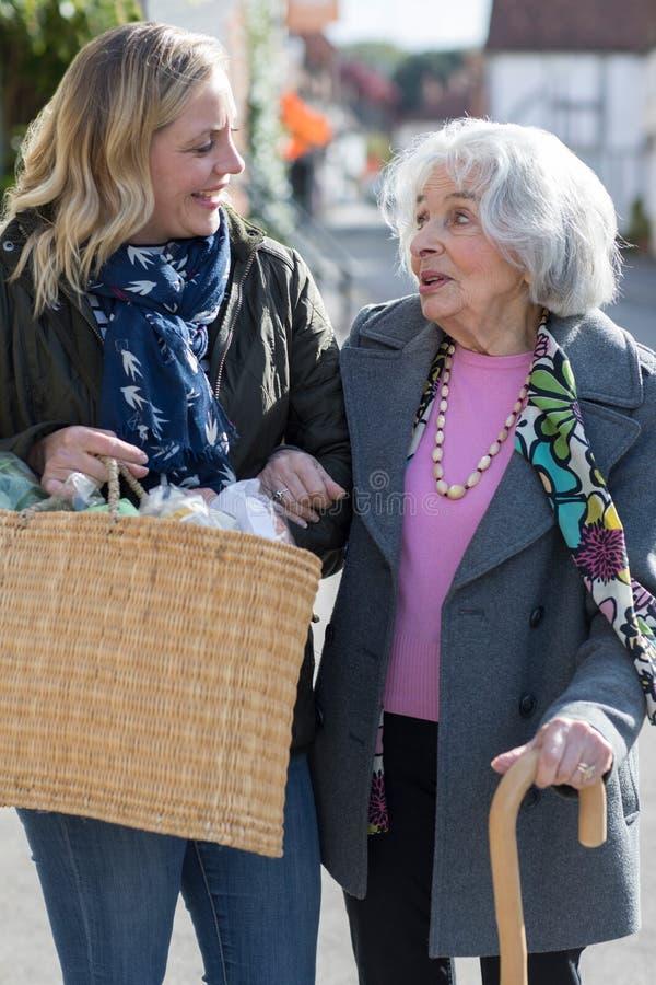 Rijpe Buur die Hogere Vrouw helpen aan Carry Shopping stock afbeelding
