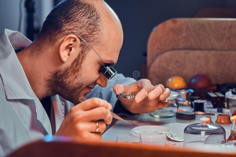 Rijpe clockmaster bevestigt oud horloge voor een klant op zijn bezige het herstellen workshop royalty-vrije stock fotografie