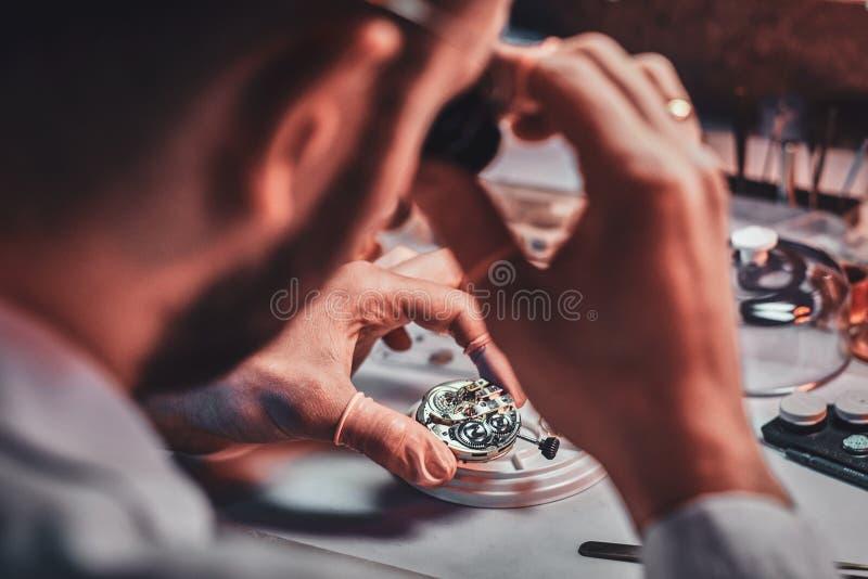 Rijpe clockmaster bevestigt oud horloge voor een klant op zijn bezige het herstellen workshop stock foto