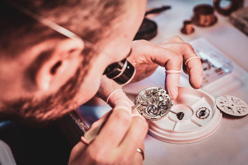 Rijpe clockmaster bevestigt oud horloge voor een klant op zijn bezige het herstellen workshop stock fotografie