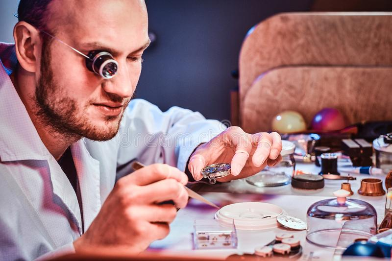 Rijpe clockmaster bevestigt oud horloge voor een klant op zijn bezige het herstellen workshop stock afbeelding