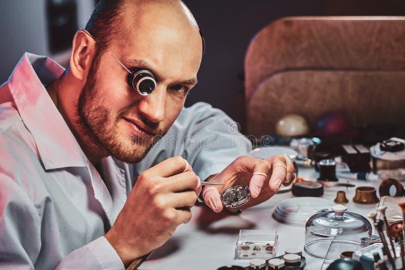 Rijpe clockmaster bevestigt oud horloge voor een klant op zijn bezige het herstellen workshop royalty-vrije stock afbeelding