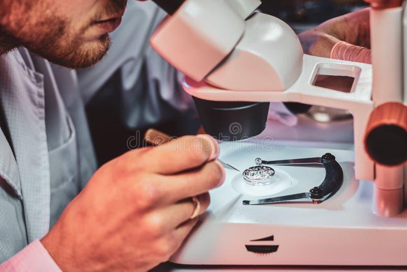 Rijpe clockmaster bevestigt oud horloge voor een klant op zijn bezige het herstellen workshop royalty-vrije stock foto's