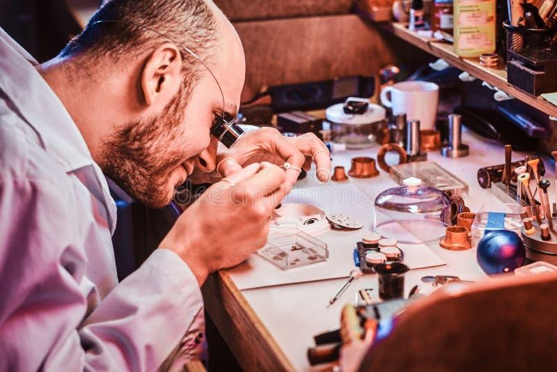 Rijpe clockmaster bevestigt oud horloge voor een klant op zijn bezige het herstellen workshop royalty-vrije stock afbeeldingen